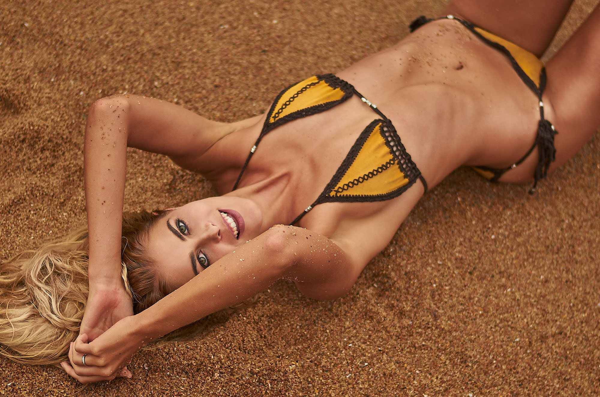 girl-lying-sand-beach-swimwear-natural